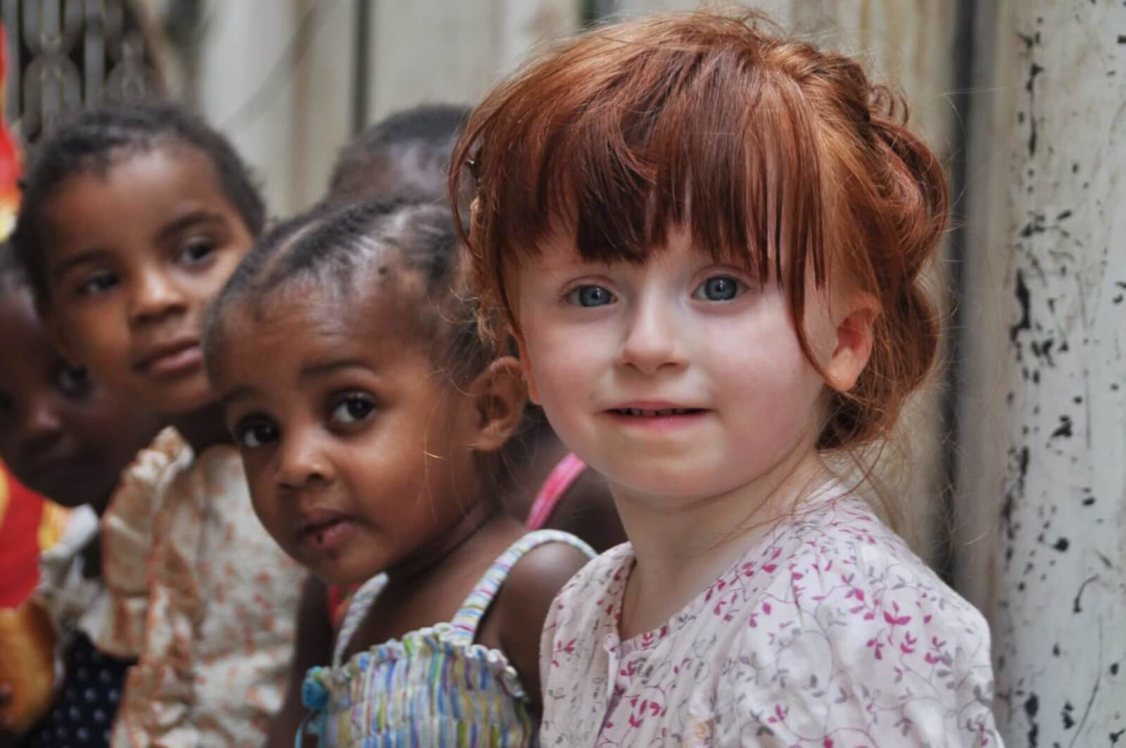 Smiling ginger-haired girl with friends from Zanzibar