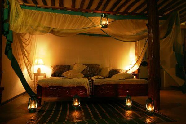 softly-lit Zanzibar villa room with petrol lamps